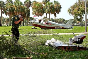 A St Petersburg police investigator takes pictures of the aircraft's left wing and landing gear after the plane crashed.
