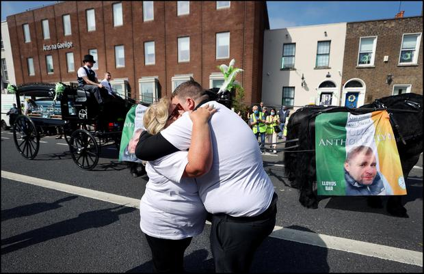 Colleagues and friends hug as the funeral                     cortege of Cllr. Anthony (Anto) Flynn passes the                     Inner City Helping Homeless offices on Amiens                     Street. Photo by Steve Humphreys