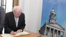 President Michael D. Higgins signing the visitors book on his arrival at St Mel's Cathedral Longford for the mass