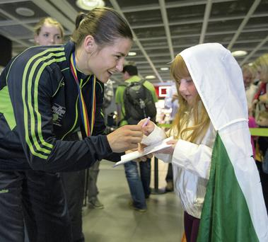 Olympic gold medallist Katie Taylor signs an autograph for Grace Carruth as she returns home to Dublin Airport after making history by claiming her sixth European title in a row with victory over Estelle Mossely of France in Bucharest. Photo credit: Fergal Phillips
