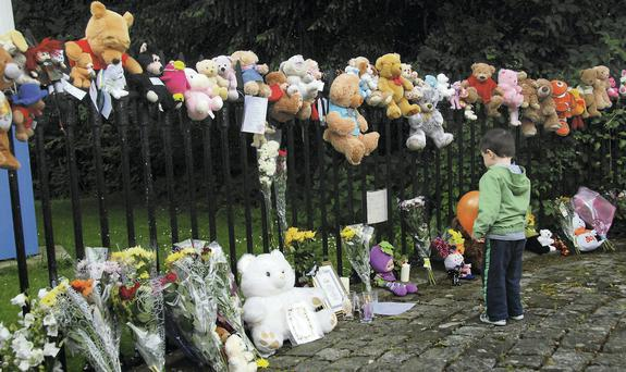 Three-year-old Cormac O'Tuama, from Mahon, looks at the teddies and flowers placed outside the gates of former Bessborough mother and bady home in Cork during the Bessborough Mother and Baby Support Group memorial service