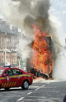 The bus in flames. Photo: Frank McGrath