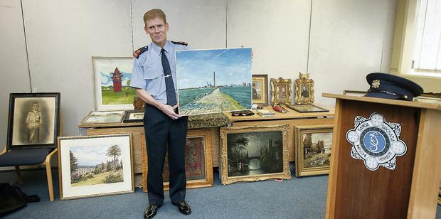 Garda Superintendent Paul Moran with the recovered artwork, believed to have been stolen years ago. Collins Photos