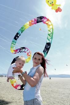 Mariola Pacek and her daughter Natalie enjoy the sunny weather at the second Kitefest event attended by more than 14,000 people at North Bull Island, Clontarf, yesterday