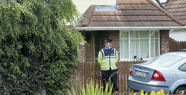 A garda outside the house in Bray, Co Wicklow, where the woman's battered body was found. Photo: Colin Keegan