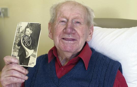 Patrick Feekery (91) with a picture of himself aged 12 when he won a gold medal in the Feis Ceoil