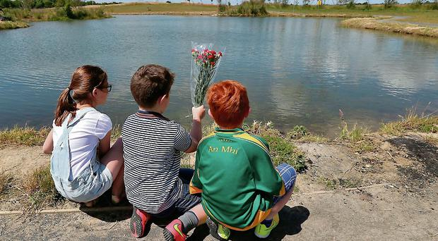 Local children, Leo Rudden (8), Callum Rudden (11) and Carol Lawrence (11) lay flowers at the manmade lake at Belgree in Tyrrelstown where 5 year old Ahmed Bari drowned