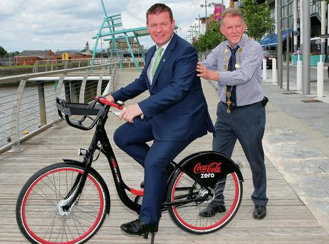 Minister Alan Kelly gets a push from the Mayor of Limerick Michael Sheahan at the unveiling of the Limerick city bikes