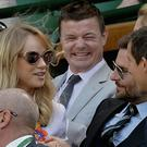 Brian O'Driscoll, centre, shares a joke with model Suki and TV presenter Bear Grylls, right, Centre Court at the Wimbledon Tennis Championships.