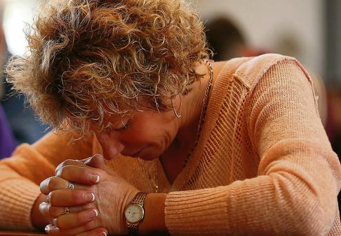 Sandra Toop, sister of Edel Mahady, prays during a memorial service for victims of the MH17 disaster