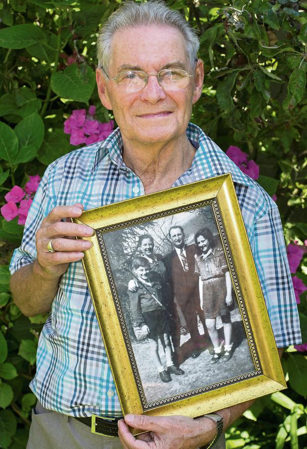 Holocaust survivor Tomi Reichental holds a pre-war photograph of himself with his parents Judith and Arnold and cousin Chava.