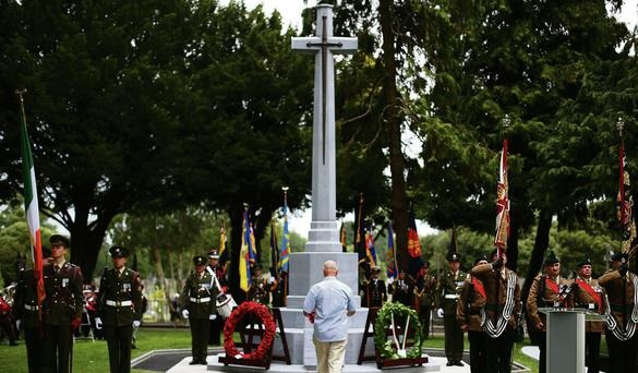 A member of the public lays a wreath at the unveiling of the Cross of Sacrifice at Glasnevin Cemetery - cemetery Masses take place annually all over the country.