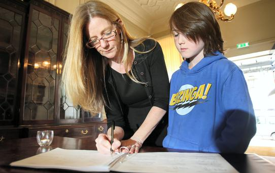 Dr Suzanne Donnelly signs the book of condolence, as her son Cuan McCauley looks on. Photo: Frank Mc Grath