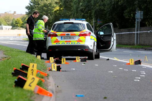 Members of the Garda Siochana Ombudsman Commission examine the Garda car which collided with a female pedestrian on the Fonthill Road near St Johns Rd in Clondalkin.