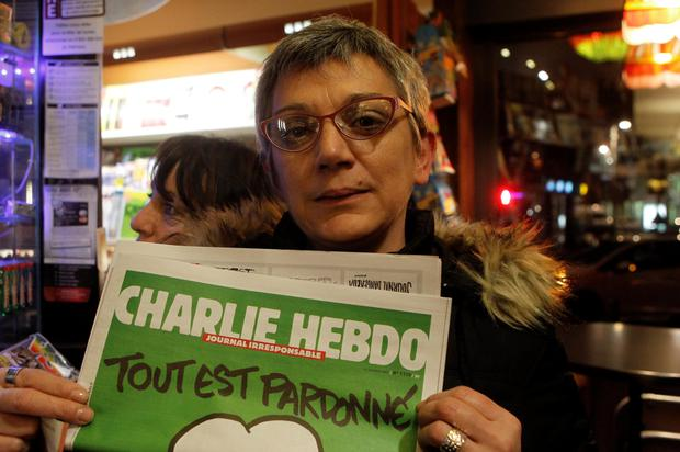 Sylvie Hajeux, 38, shows the front page of Charlie Hebdo newspaper at a newsstand in Lille