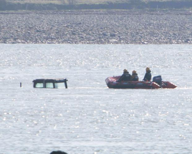 A Coast Guard team surveys the submerged cabs of the tractors in Poulnasherry Bay
