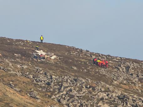 Mountain rescue teams recover the bodies of the two men. Below, Bryan Keane, who died in the crash