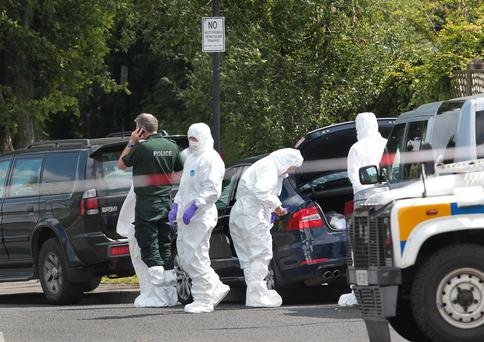 Police and forensics at the scene in Derry after a bomb was found under the car of a serving PSNI officer
