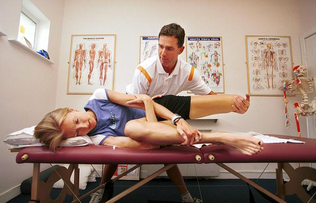 Physiotherapist Gerard Hartmann massages champion runner Paula Radcliffe's foot at his clinic in Limerick