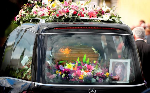 ALWAYS SMILING: A picture of nurse Lorna Carty with a beaming smile adorns her coffin surrounded by flowers as the nurse and Dunderry stalwart is laid to rest after being tragically killed in a terror attack in Tunisia