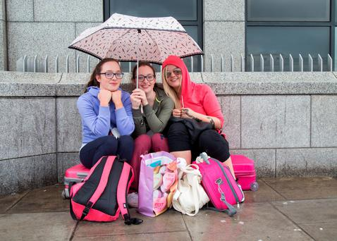Sisters Laura and Rachel Kelly and Lisa McDonald waiting in the rain on Custom House Quay in Dublin for the Wexford bus