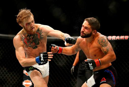 Conor McGregor, left, punches Chad Mendes during their interim featherweight title mixed martial arts bout at UFC 189