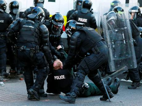 A PSNI officer goes down injured after being hit by an object thrown by a loyalist protester