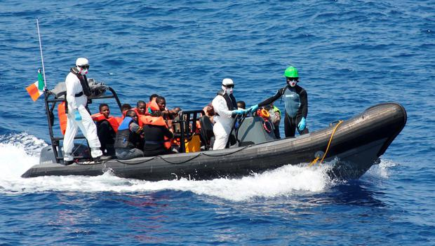 Crew members of the LÉ Niamh rescue migrants in the Mediterranean