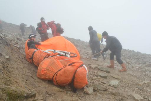 A member of the Mountain Rescue Team joins others inside an orange bothy (storm shelter) near their wrapped up equipment on the slopes of the cone of Croagh Patrick near Murrisk, Co Mayo