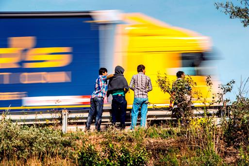 A truck passes as migrants stand beside the road in Calais, northern France