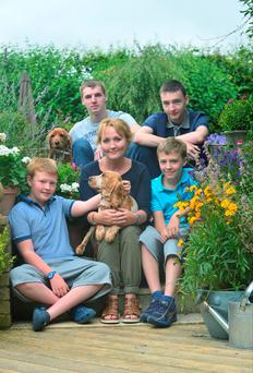 HAPPY FAMILY: Ruari, Cillian, Lisa, Oisin and Ronan Freeney with their dog Millie, who they got from the Carlow puppy farm, pictured at her new home in Athgarvan, Co Kildare. In the backround is the family's other pet, Fudge
