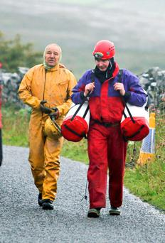 Patrick Troy and one of his rescuers after he and his son Finn were rescued from a cave in north Clare yesterday after being stuck for 28 hours