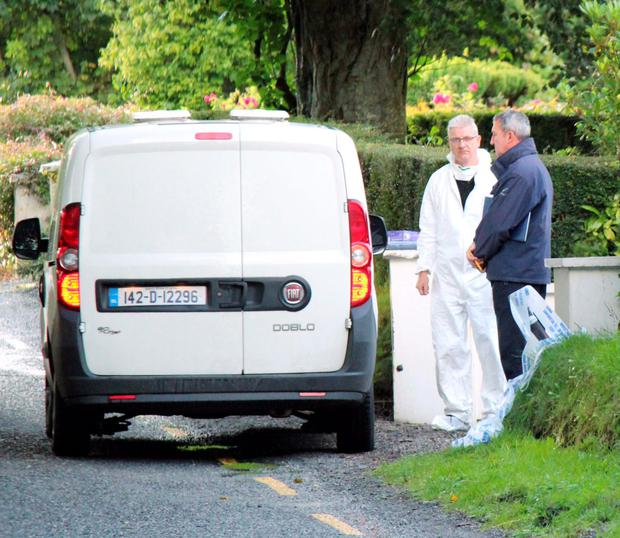 Gardaí at the scene in Doon where John O'Donoghue collapsed and died after being confronted by intruders at his home