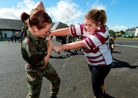 Irish Independent reporter Emma Jane Hade gets to grips with Instructor Pt Stacey Kehoe during a fitness session as part of the 17 weeks basic training for new Irish Defence Forces recruits at Stephens Barracks in Kilkenny