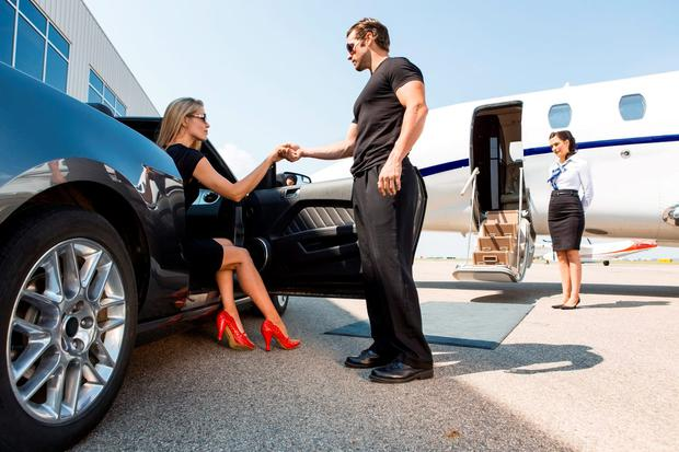 Full length of bodyguard helping elegant woman stepping out of car at airport terminal