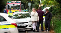 People gather at the scene of the tragic fire at Glenmaluck Road, Carrickmines, this morning