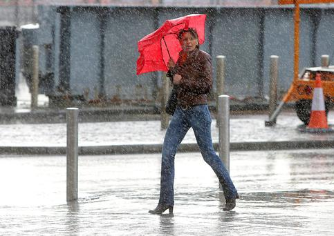 A woman gets caught in heavy rain in stormy conditions in Dublin city centre