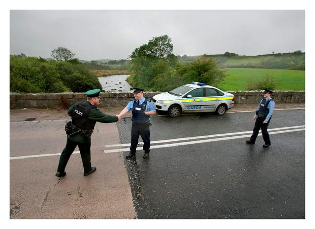 Garda Robbie Peelo shakes hands with a PSNI officer on the Louth/Armagh border prior to setting up a joint checkpoint, as Garda Emma Kelly looks on