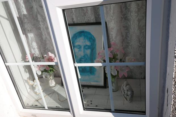 A religious picture in the window of the house in Faythe, Co Wexford where the body of the elderly woman was found