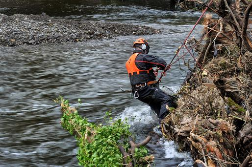 A worker removes debris from River Bandon in Co Cork yesterday in the clean-up operation following Storm Desmond
