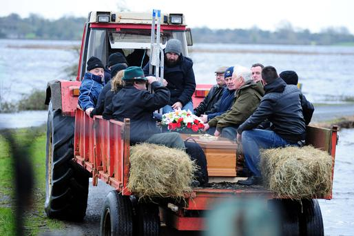 Mourners travel with the coffin and in a cattle trailer as the remains of John Clarke are transported to Saints Island Graveyard, Co Longford, which was cut off due to flooding. Photo: James Flynn/APX