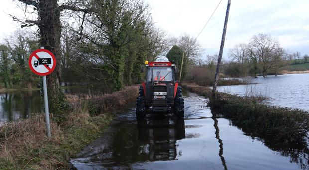 Cavan farmer Simon West makes his way through the flood waters that surround his home at Derryheen. The county is under threat of further flooding. Photo: Lorraine Teevan