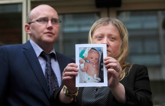 Maree Butler and Eoin Byrne hold a photo of their son, Darragh, at the inquest into his death. Photo: Gareth Chaney