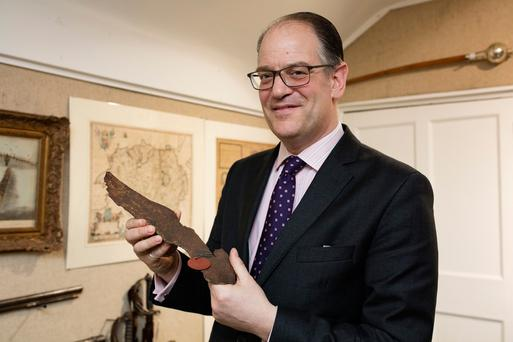 Stuart Purcell of Whytes Auctioneers with a piece of shrapnel from a German WWII bomb that landed in Terenure Photo: Arthur Carron