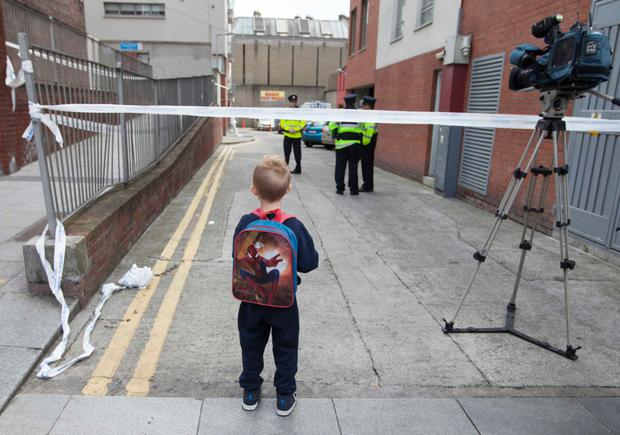 No entry: a seven-year-old boy looks beyond the cordon after another gangland shooting in the north inner city of Dublin in 2017. Photo by Eamonn Farrell