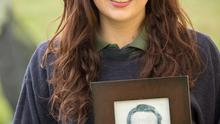 Bethany McLoughlin, who is singing with the Ursline school choir to sing for Charles and Camilla at Drumcliffe Chapel, Sligo on Wednesday with a photo of her grandfather Gerard Mc Kinney who was shot dead by the Paratroopers on Bloody Sunday In January 1972, at her home in Sligo, yesterday. Photo: James Connolly