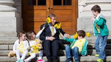 Taoiseach Enda Kenny is presented with daffodils from twins Cate and Emily Cobbe (aged 4) and Jack and David Williams (aged 5) all from Bray, Co Wicklow
