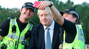 ELECTION IN SIGHT: British Prime Minister Boris Johnson poses for a selfie with police officers in England on Friday