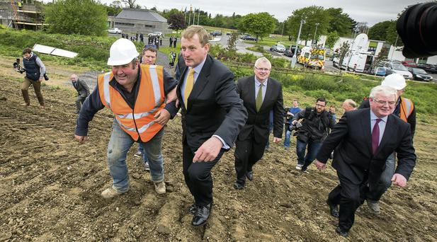 Enda Kenny and Eamon Gilmore pictured with foreman George Browne at Abbotstown in Dublin yesterday