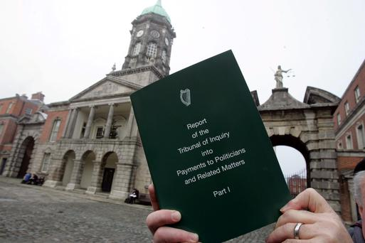 A copy of the Moriarty Tribunal Report is held up at Dublin Castle. Photo: Tom Burke